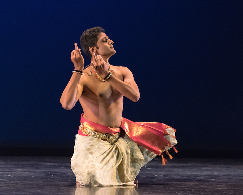 A bare-chested male Indian dancer assumes a kneeling position while his hands and fingers make a gesture near his face.
