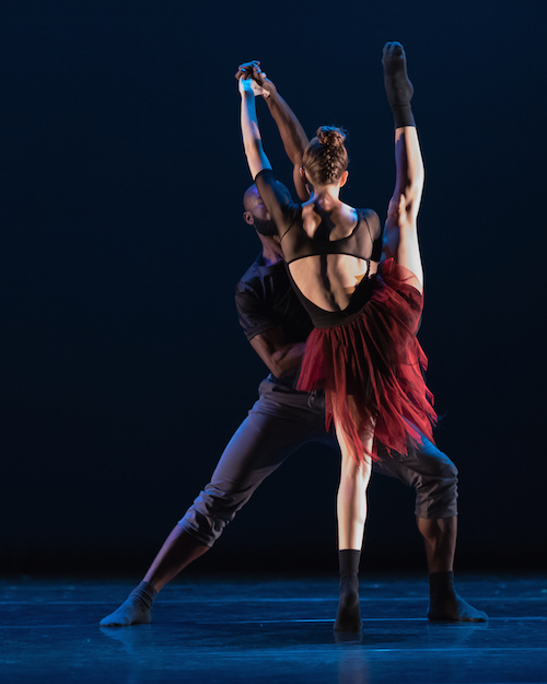 A women extends her right leg in a high developpe with her back turned to the audience. She wears a deep red skirt, intricate black leotard and black calf length socks. Her male counterpart helps her balance by grasping her hands.