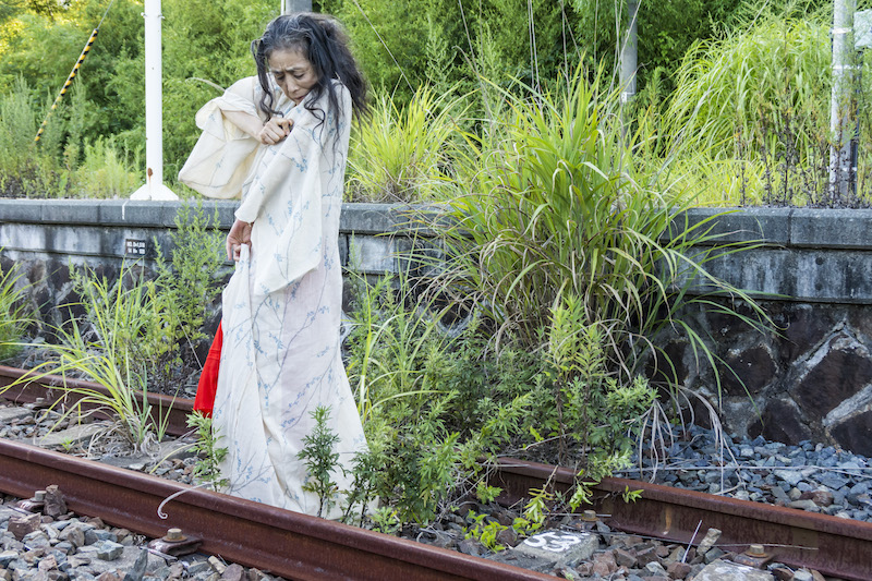 Eiko walks on the railroad tracks in Fukushima, she pinches her robe at the shoulder