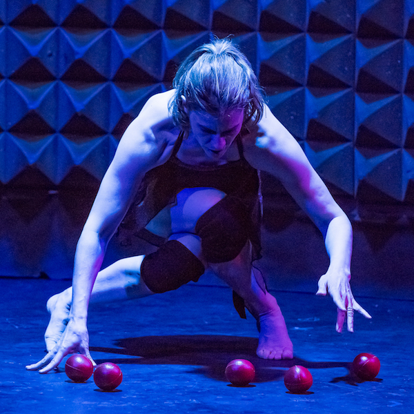 Ellis Wood crosses her legs at the knees and crouches over four red small rubber balls