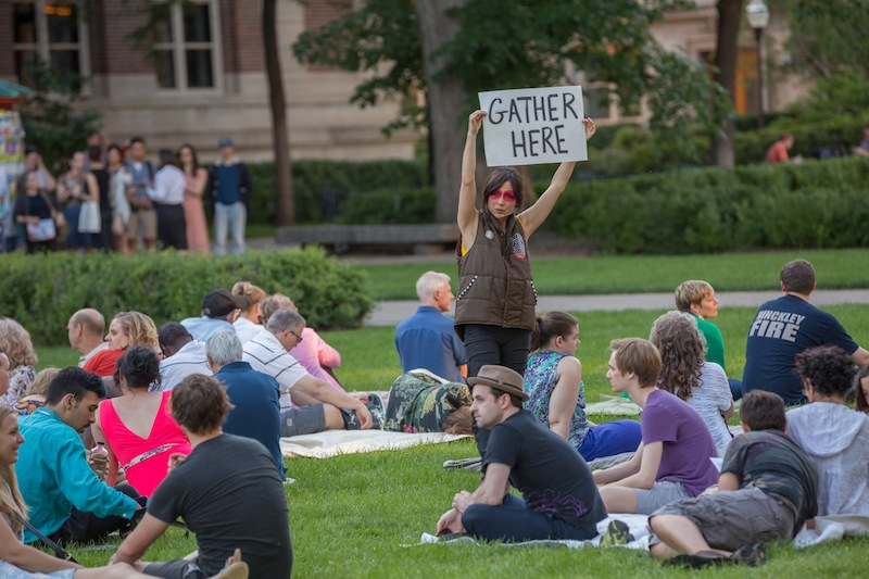 Emily Johnson holding a sign that says: gather here amongst a group of people sitting on grass
