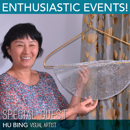 Visual Artist Hu Bing smiles next to one of her creations which includes an iron clothes hanger and blown glass