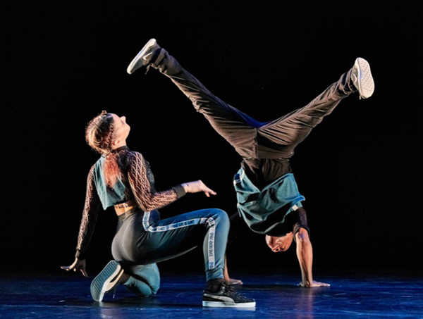 A woman kneels while a man executes a wide-legged handstand