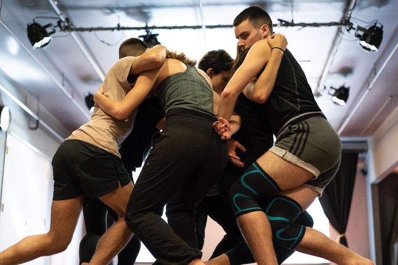 A group of dancers in rehearsal clothes huddle in a mass