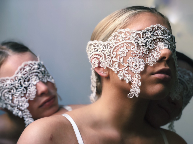 Two women wear lace over their eyes like a blindfolds