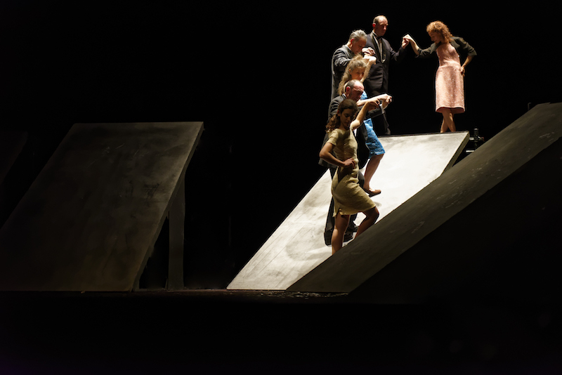 Dancers stand on ramps that are at various levels on stage. They hold hands doing a grapvine motion.