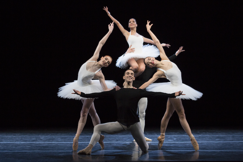 Dancers in white classical tutus pose in a tableau. One man is on his knee, two women are en pointe with the arms outstretched. And another male dancer lifts a woman onto his shoulder.