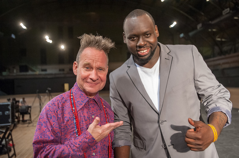 Directors Peter Sellars, in a bright pink and blue button up and beads, and Regg Roc, in a grey suit, pose together