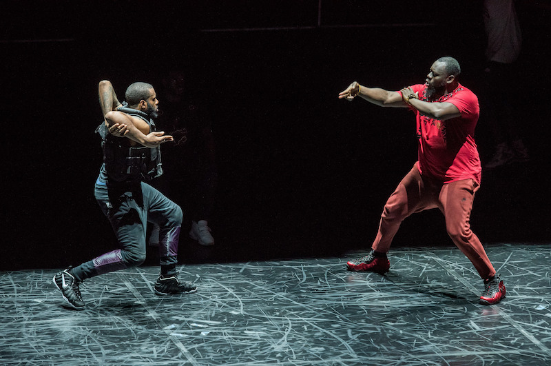 Two flexn dancers face one another. One has his elbows bent behind his upper back. His legs are in a crouched position. Another dancer, in all red, faces him, his right arm gestures to his counterpart.