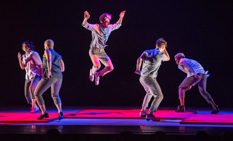 A dancer leaps in the air with arms near his head. Other dancers in cropped beige pants and button up shirts tap near him. Lights cast a hot pink glow on floor they dance upon.
