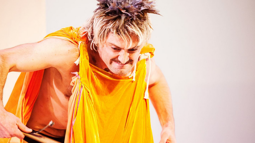Dancer Sean Donovan wearing a turmeric-colored tunic and grinning/grimacing.