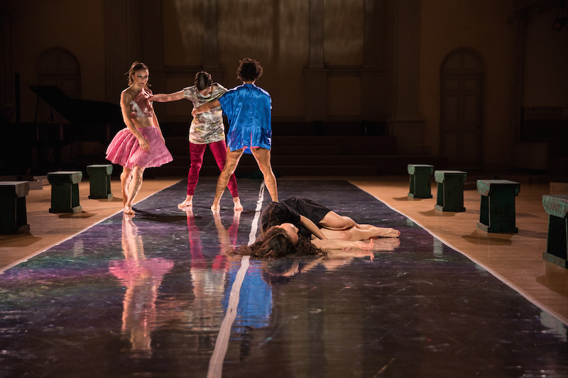 Three women stand close to one another in the background. One's palm press against another's shoulder. A woman in pink looks down at dancer in the distance who is laying down.