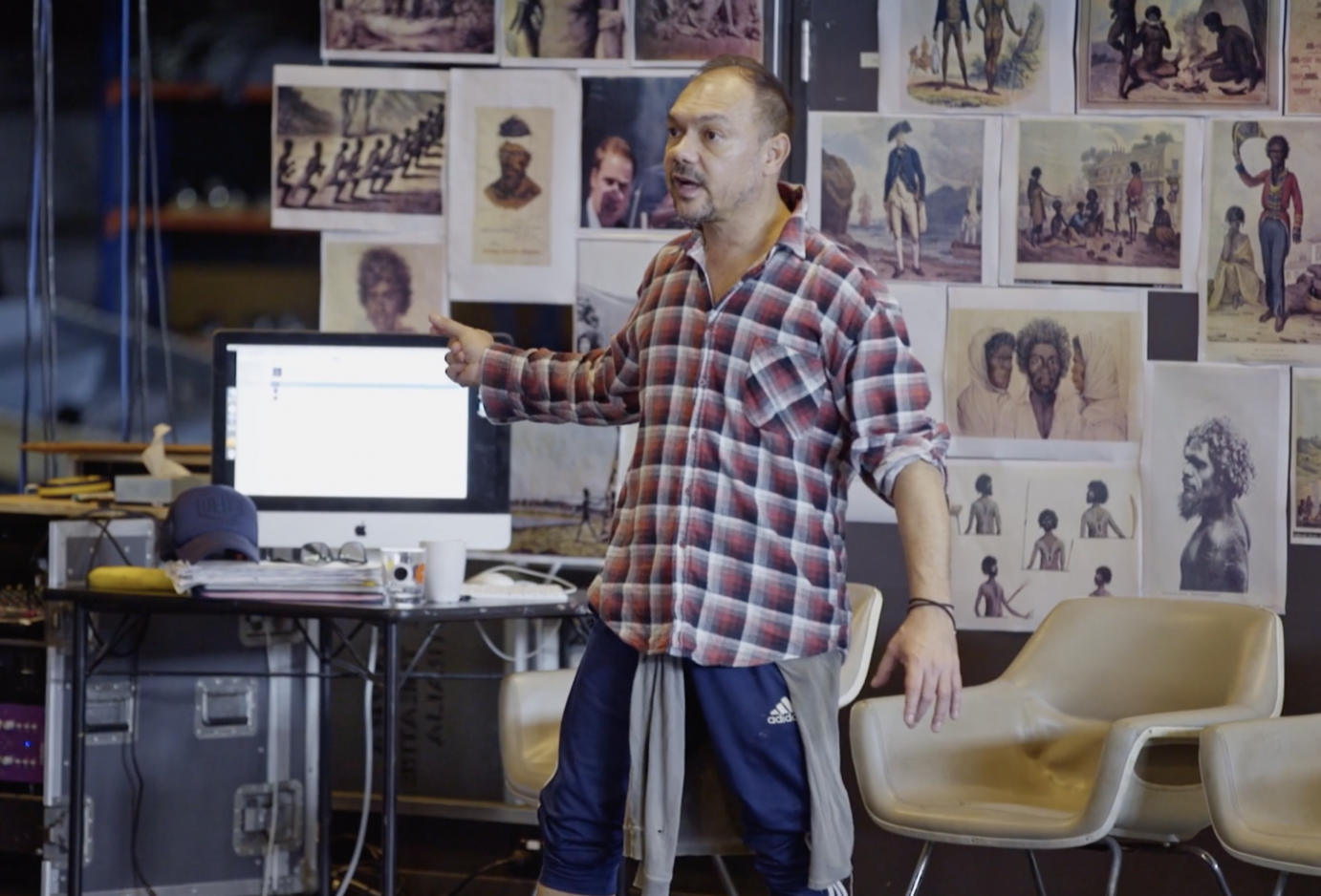 A man in a flannel  shirt stands in front of a wall of pictures, directing dancers