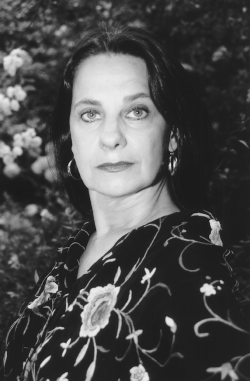 A black and white headshot of Carlota Santana. She sits in front of a floral background and wears a dark floral blouse.