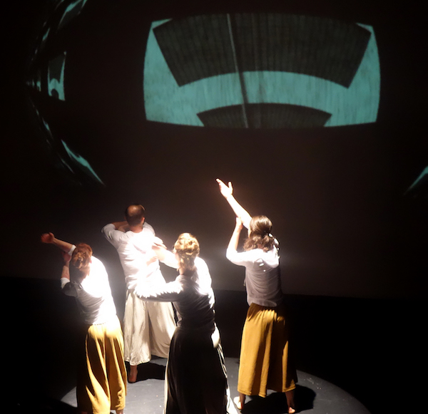 Four dancers in white shirts and yellow pants face the upstage wall which has a geometric projection