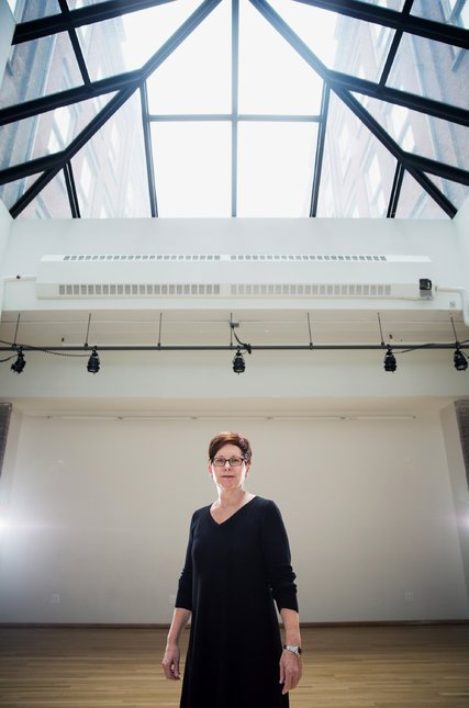 Gina Gibney standing beneath a skylight within Gibney Dance at 280 Broadway.