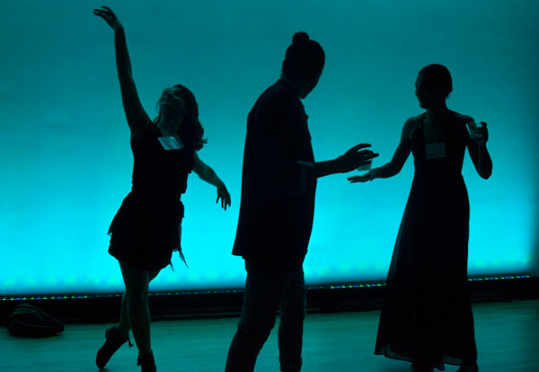 Silhouettes of three dancers against teal lighting.