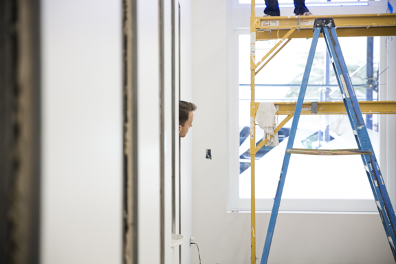 A man peeks his head into a studio where a ladder has been set up for construction.