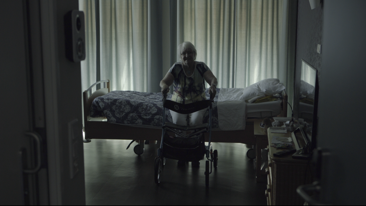 Gabri Christa's mom, Magdalena sitting on the edge of a bed with her walker, a still shot from Christa's film
