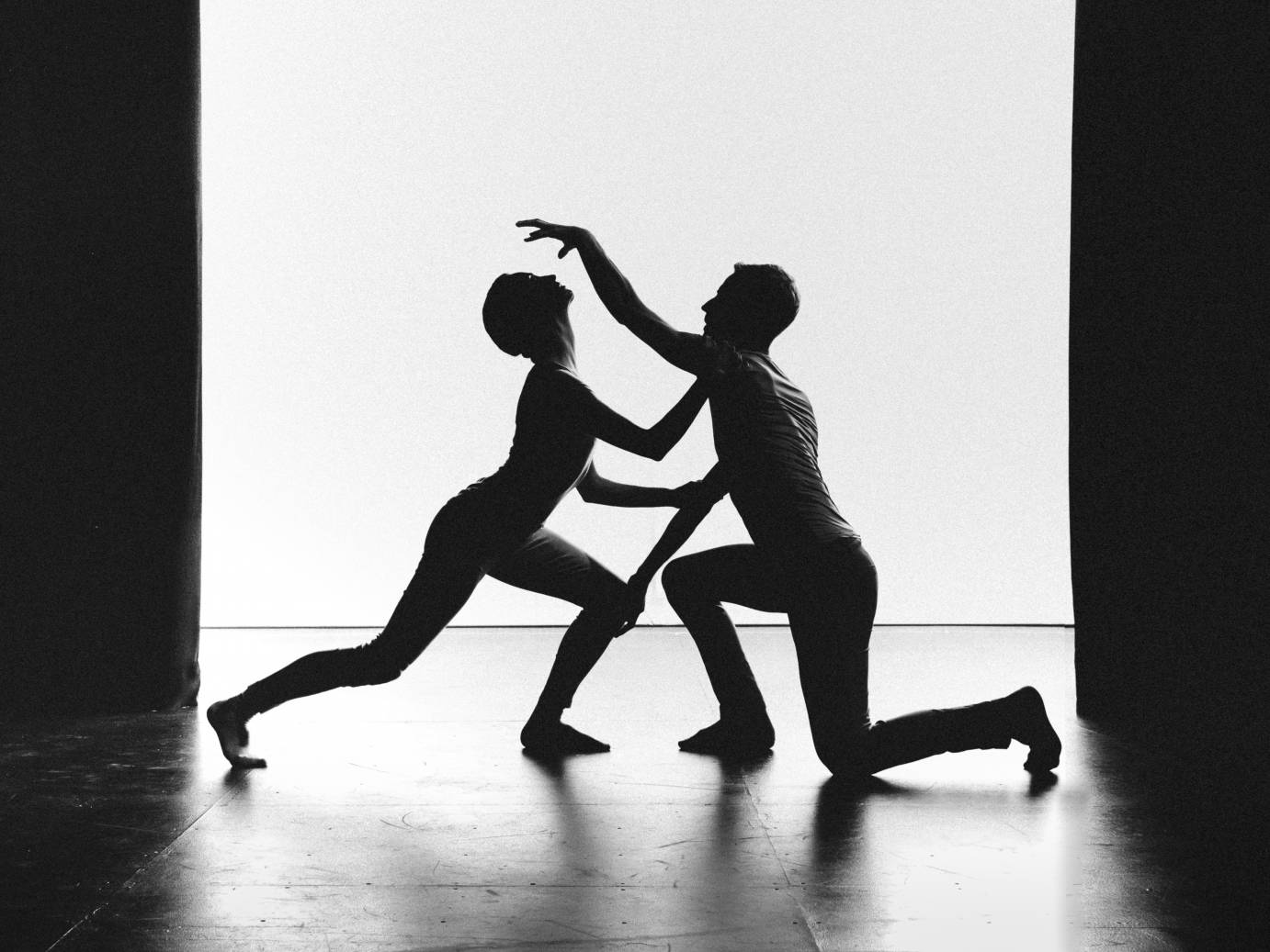 In profile, two dancers lunge facing each other as one lifts a hand above and the other lifts her lips