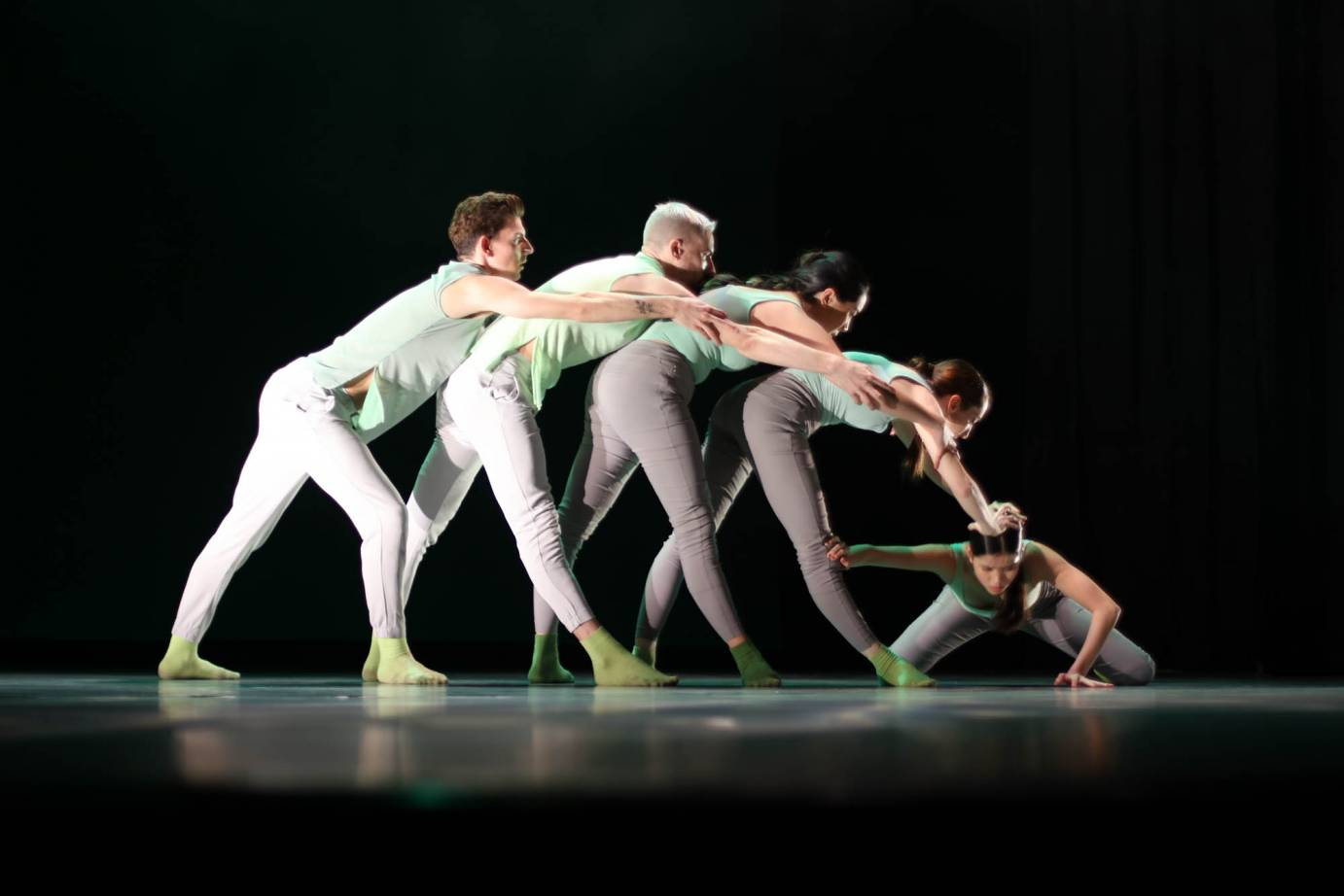 Dancers fold over each other in a line with one kneeling dancer grabbing the knee of the leader