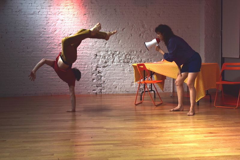 Gabrielle speaks into a megaphone while Aleksandr flies upsidedown in a a part cartwheel, part handstand.