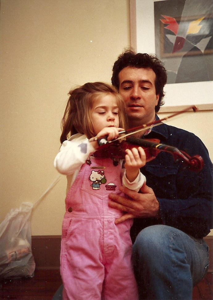A father kneels beside his young daughter in pink overalls as she plays the violin