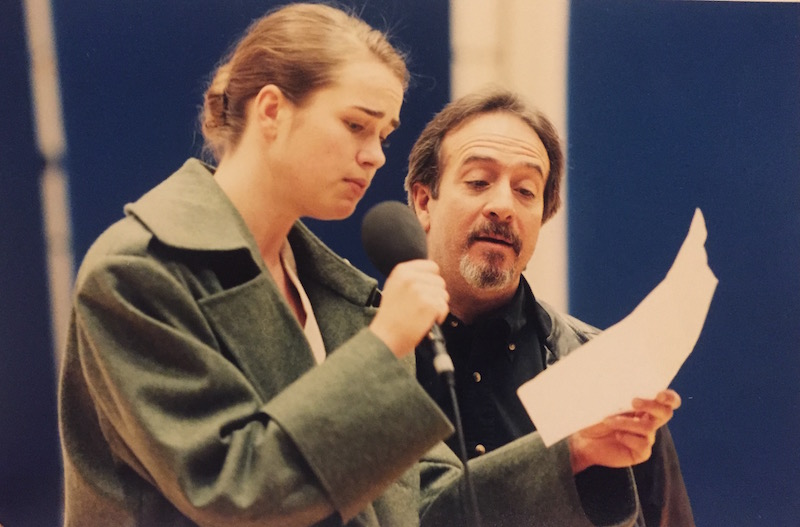 A bearded Michael Galasso stands next to a female performer who wears an overcoat and speaks into a microphone. They both are looking at a piece of paper.