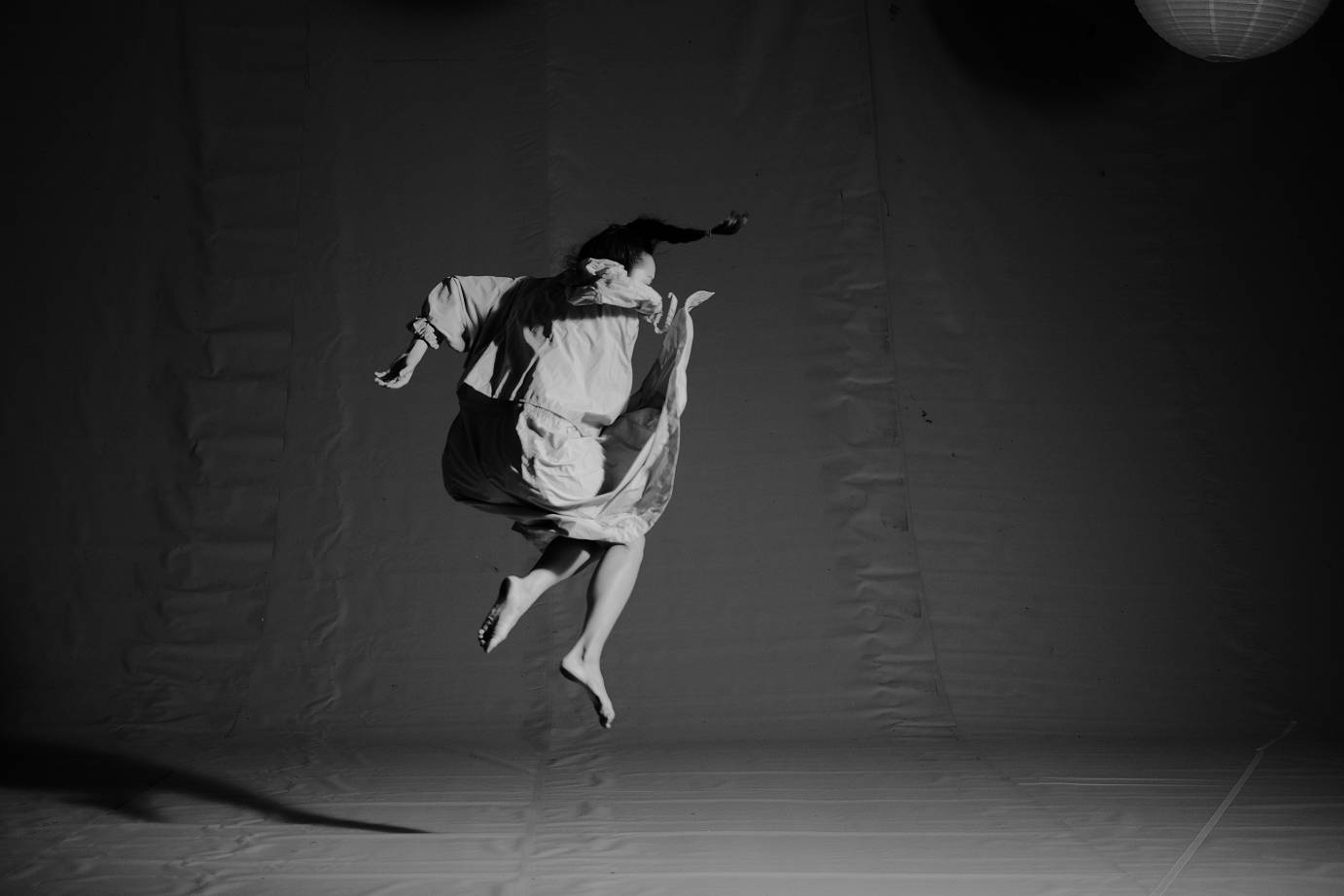 Black and white photo of a girl jumping