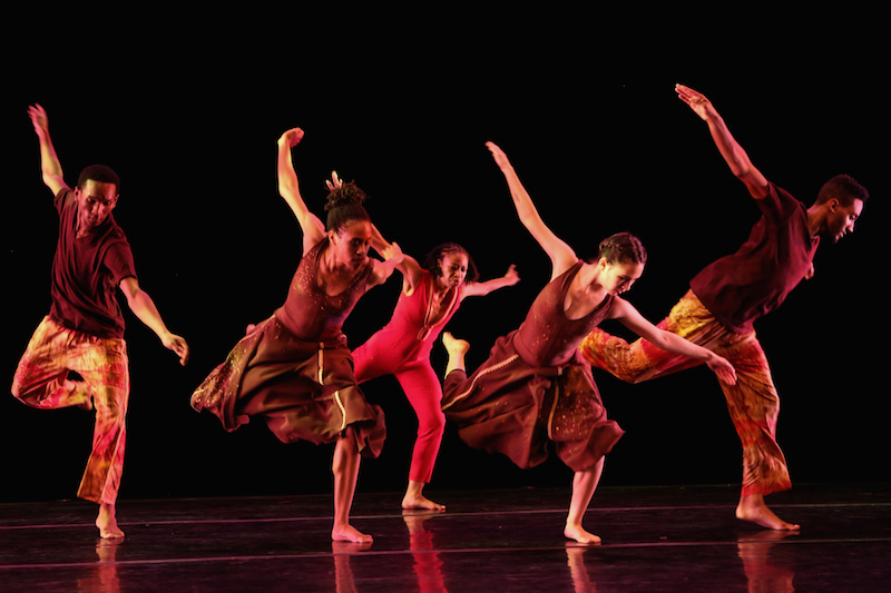 A group of five dancers wearing shades of red stand on one leg. Their arms are outstretched like wings and their other leg is bent behind them.
