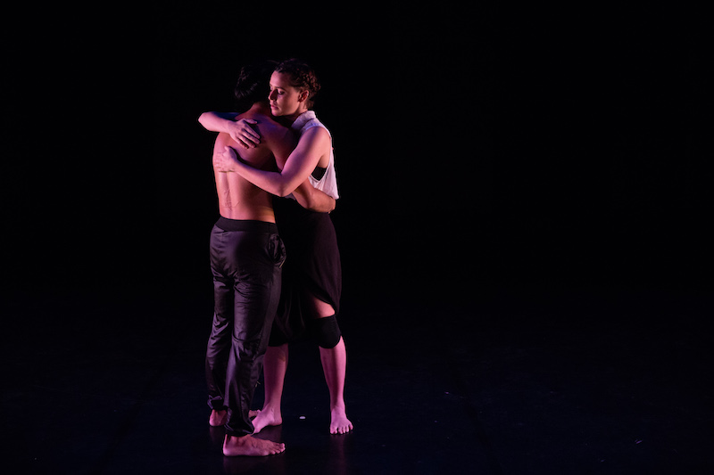 Two figures embrace. One is shirtless and other wears a white blouse and black bottoms.