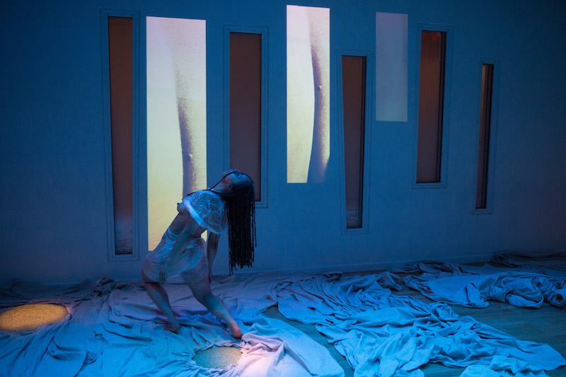 Samantha Speis hinges at her hips. White fabric is strewn across the floor. Two video projections are cast on the wall.