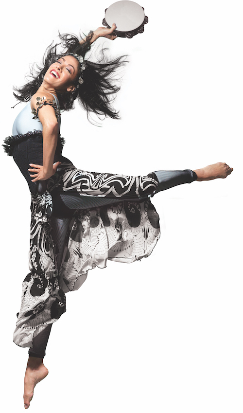 Parisa with her hand on her hip kicks her left leg behind her in an attitude position. She wears a gypsy inspired costume.