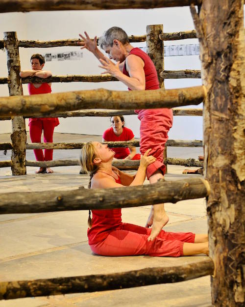Mendl Shaw with dancers dressed in red dance in a gallery space that is enclosed by a wooden fence