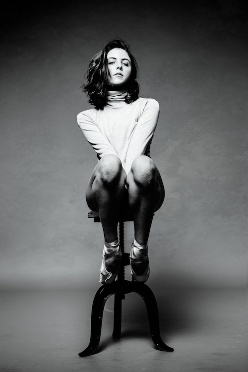 Gianna Reisen sits on a stool wearing a turtleneck and pointe shoes in a black and white photo.