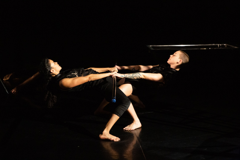 Two dancers hold hands facing one another and hinge their upper bodies parallel to the floor.