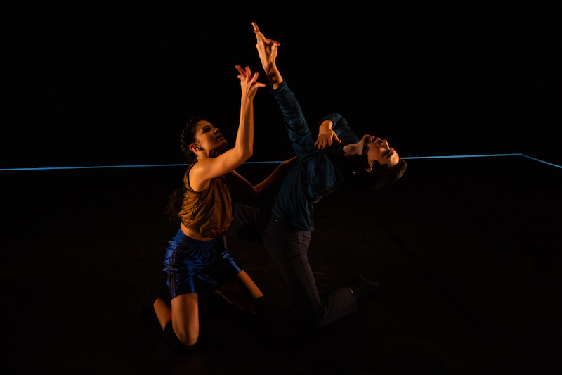 Two dancers, in semi darkness, kneel facing one another and reach each of their arms to the ceiling.