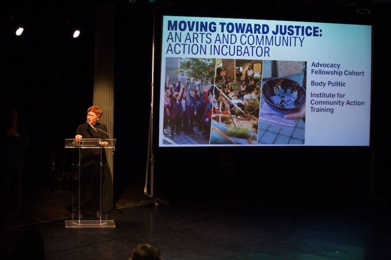 Gina Gibney stands at a podium describing the organization's new programming. A screen projections information about the new arts and community action incubator.