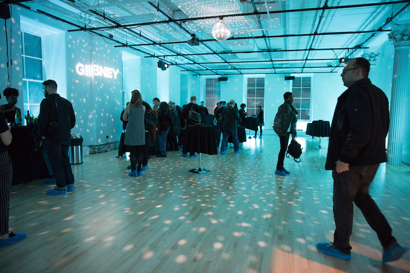 A crowd of people mingle in one of Gibney's new studios. A disco ball hangs from the ceiling casting an ice blue glow. The organization's new block-lettering logo 'GIBNEY' is projected on a wall