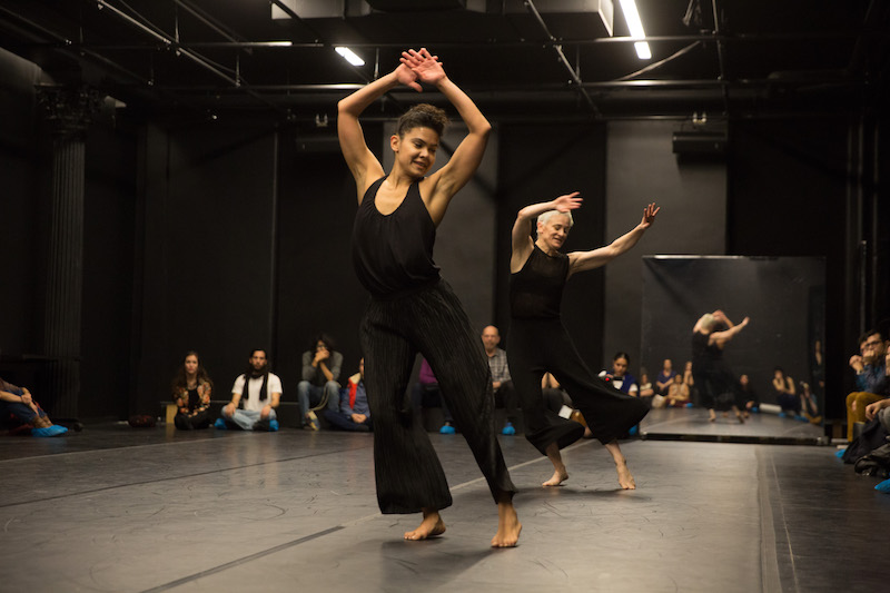 Two women in black tanks and pants dance with their arms above their heads. People sit around them and watch.