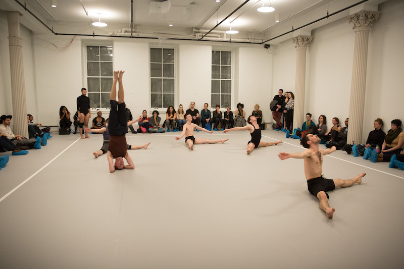 Dancers sit on the ground with their legs splayed. One stands on their head. Audience members line the studio's perimeter sitting and watch.