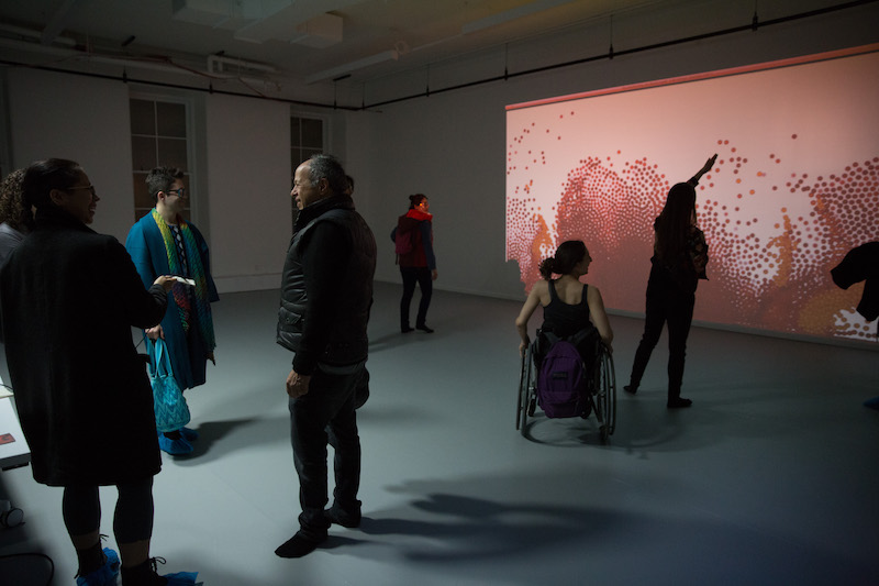 A group of people take in one of Gibney's new studios. A salmon colored screen with dots is projected on a wall.