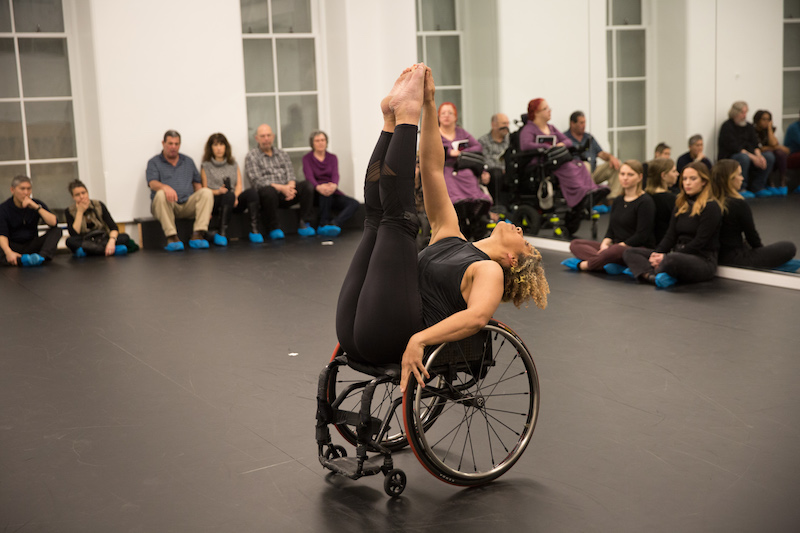 A woman raises her legs to sky as she extends back in a wheelchair. People sit on the floor and watch her in a Gibney studio.