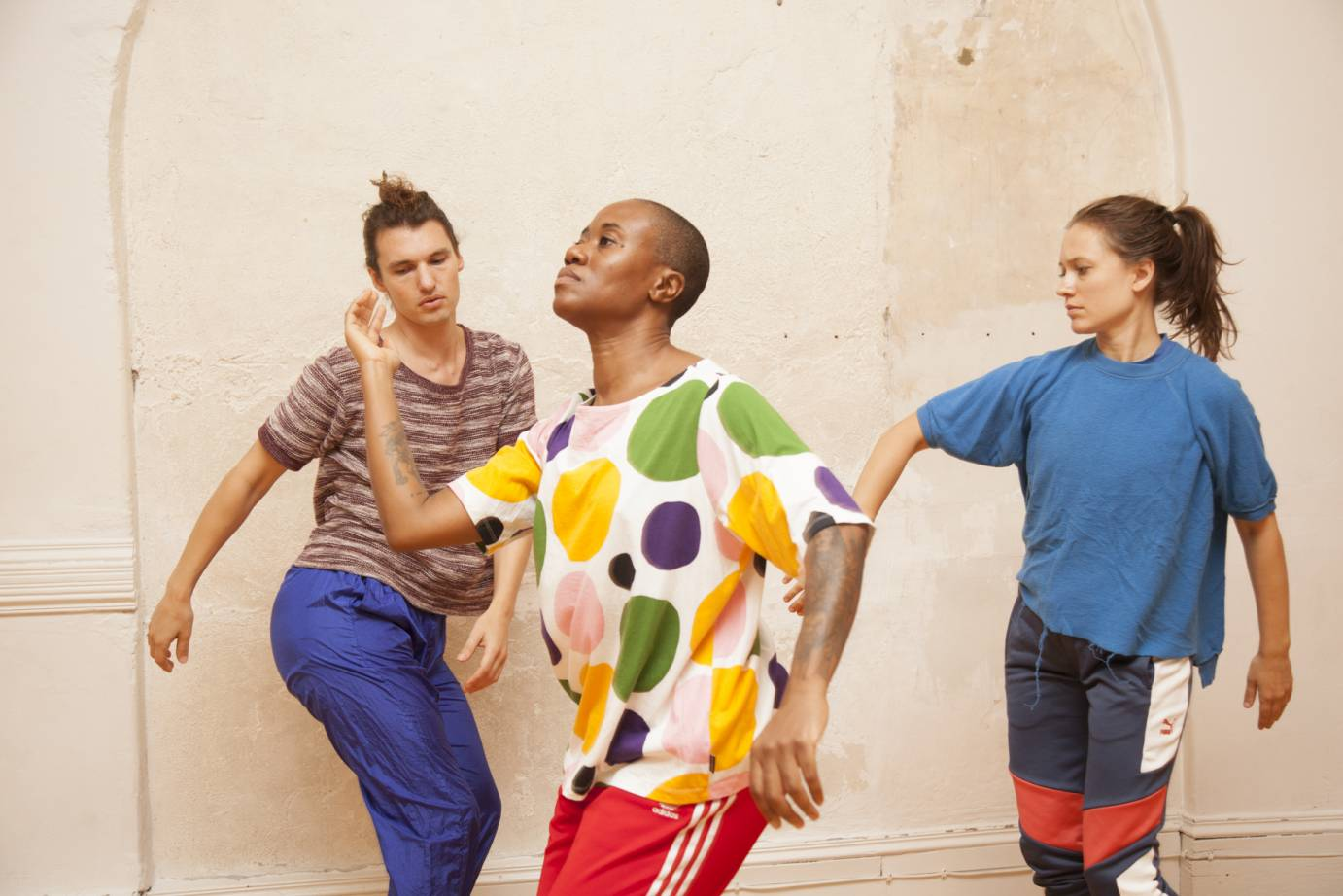 Three dancers in bright shirts