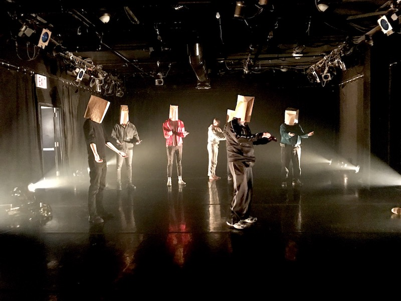 A group male audience members stand on stage with paper bags over their heads. Their arms are out in front of them.
