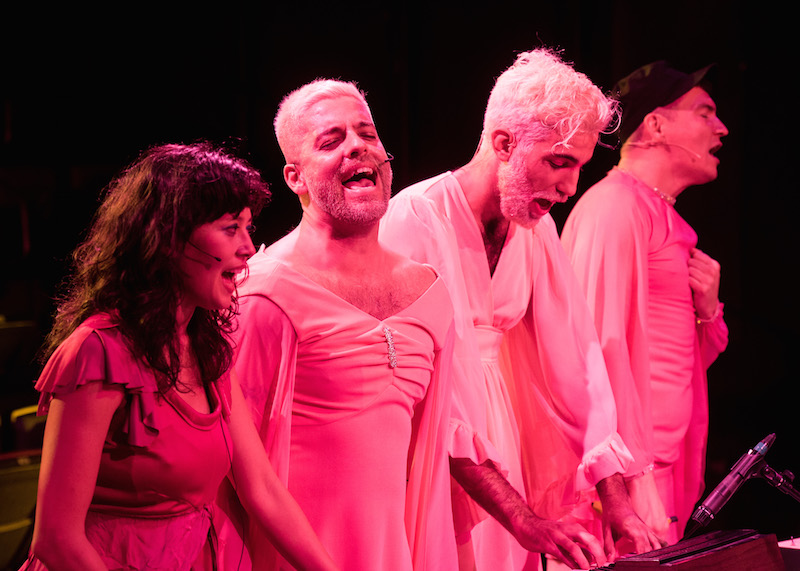 The performers of Part 2, cast in a pink light, sing towards the audience