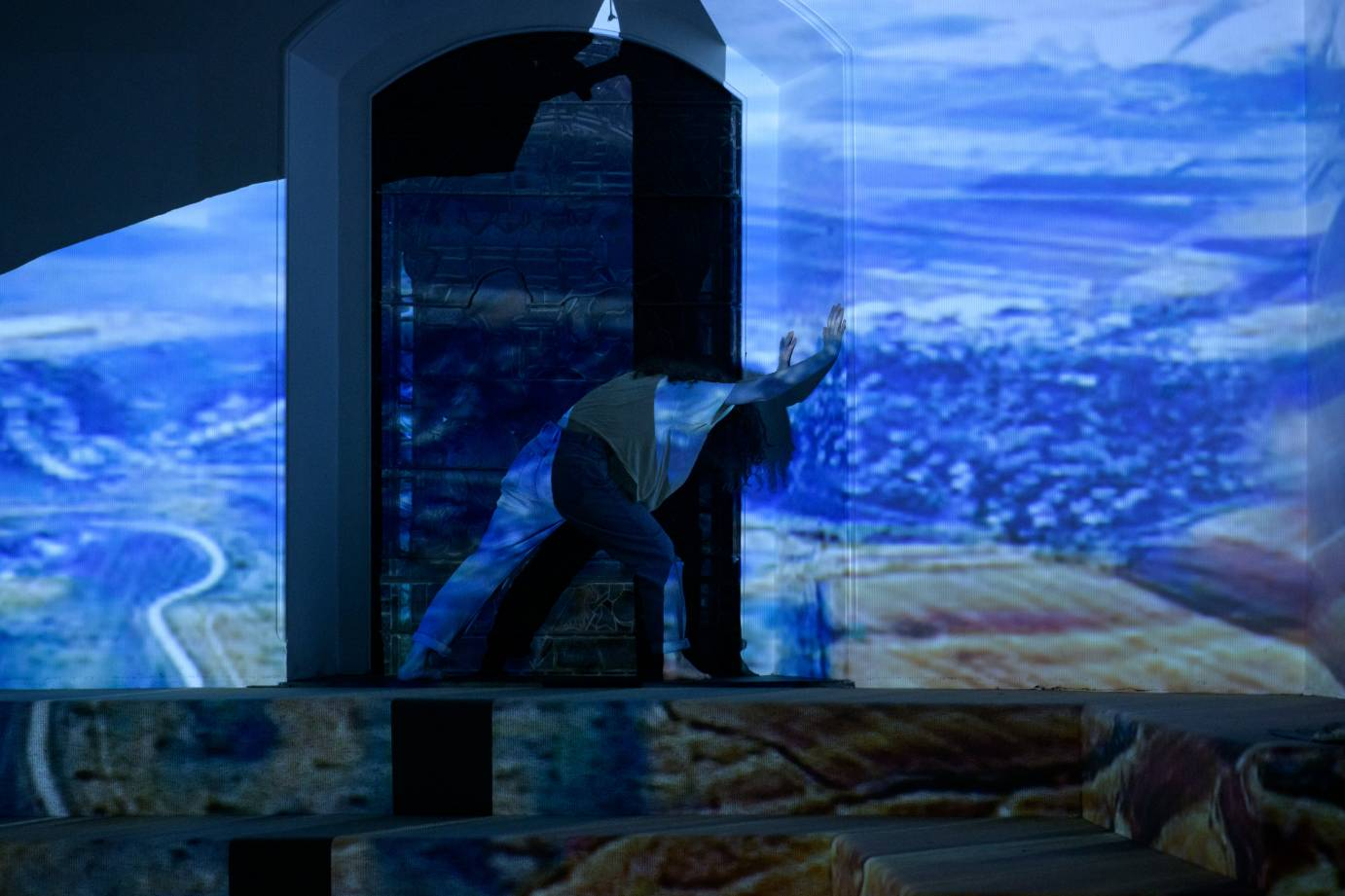 A woman lunges against a nave, drenched in a projection of a landscape