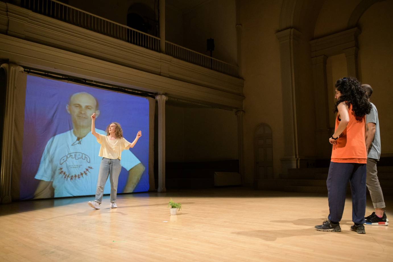 A woman dances in front of a projection of a man while people watch