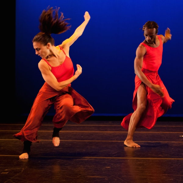 Two dancers in red costumes in a flurry of dynamic movement. One dancer's pony tail is lifted into the air.