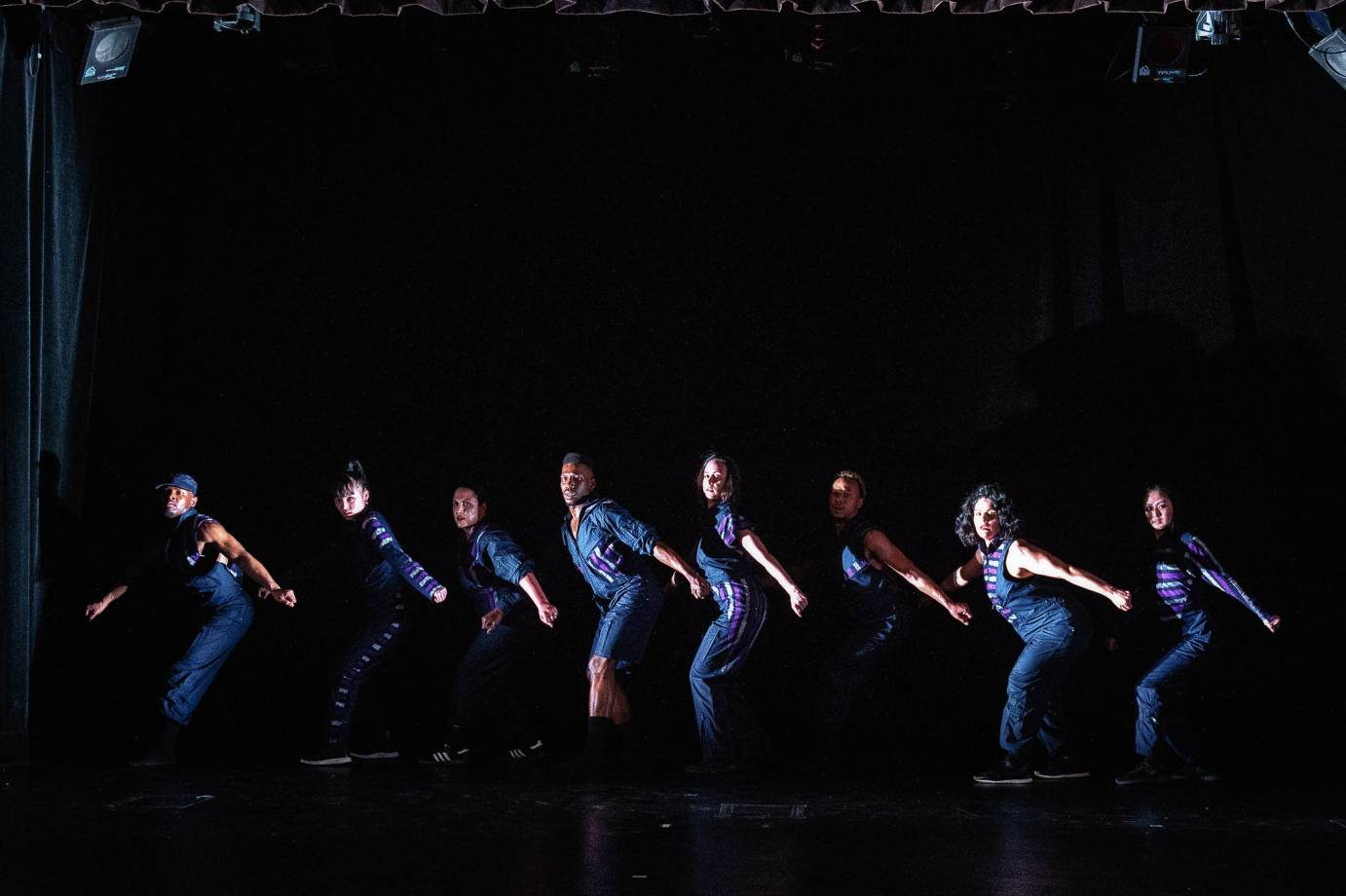 Dancers stand in a line, back arched, knees bent